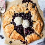 rustic blueberry pie (blueberry galette) on parchment paper with two scoops of ice cream