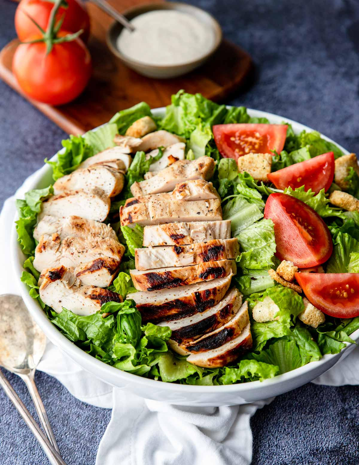 grilled buttermilk chicken on top of a salad