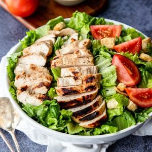Grilled Buttermilk Marinated Chicken on top of a salad with tomatoes and croutons