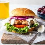 grilled pork burger with lettuce, onion, tomato on a bun