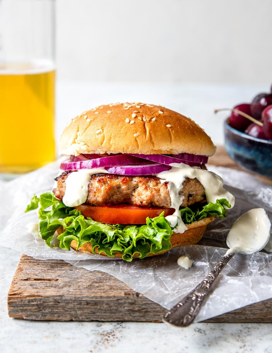 Grilled Pork burger on a bun with garlic cream sauce, tomato and lettuce