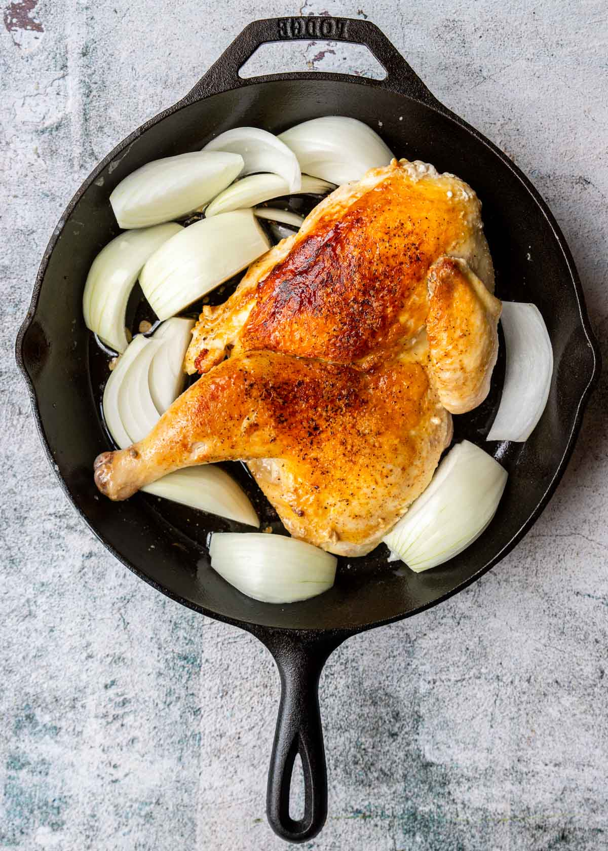 half chicken in cast iron pan with onions