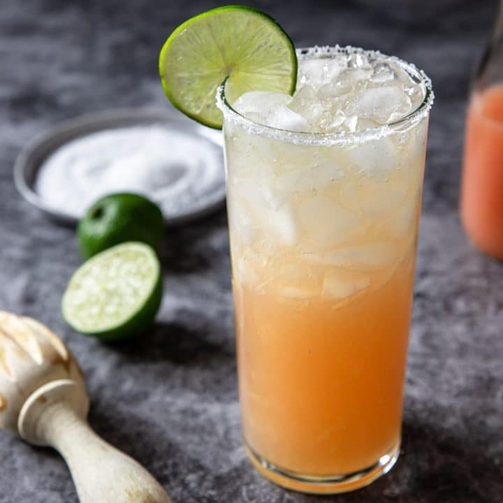 Paloma in a tall glass with lime wheel and salt on the rim