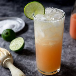 Paloma cocktail in a tall glass with salt on the rim and a lime garnish