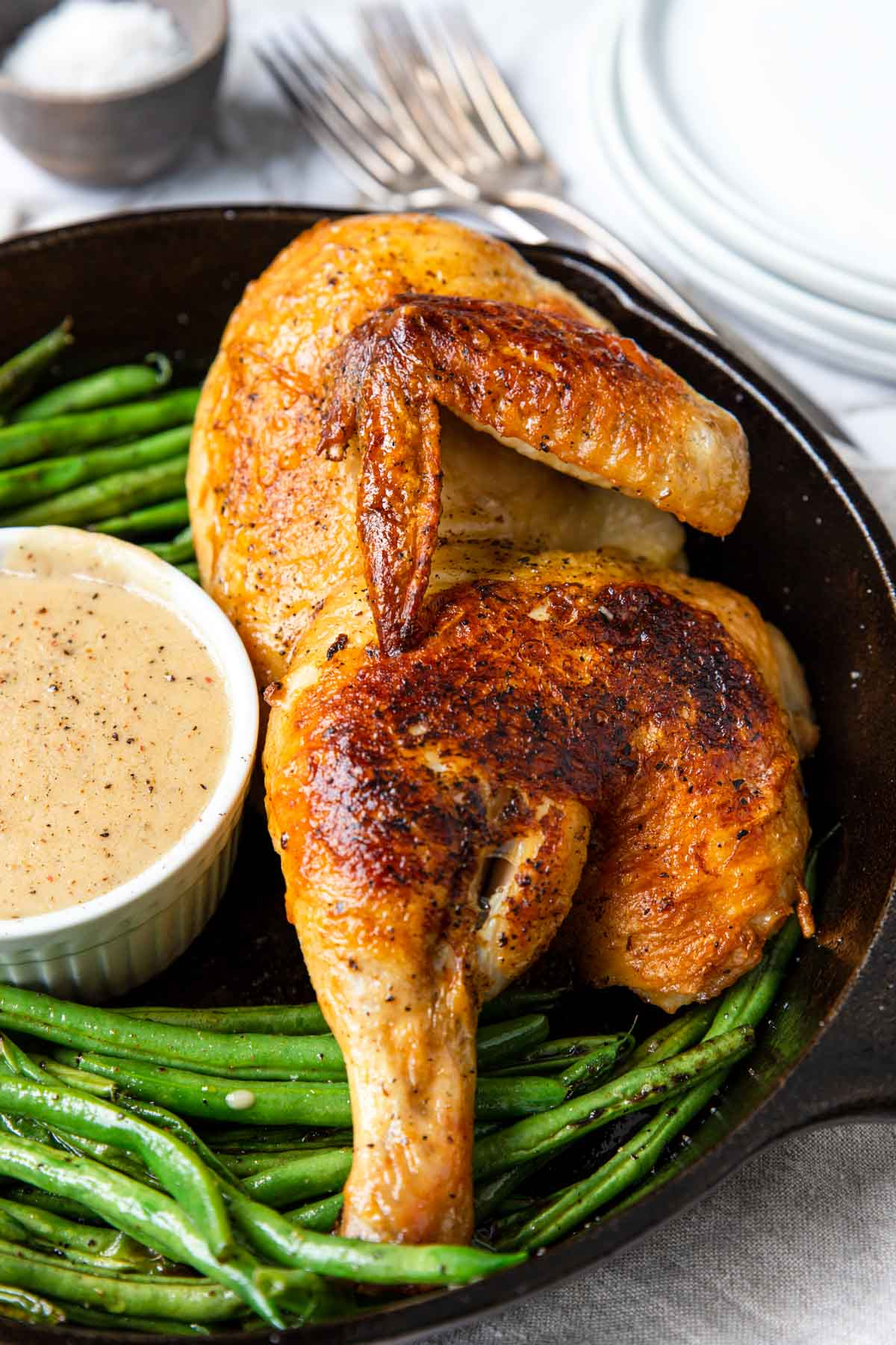 half chicken in a cast iron skillet with green beans and gravy