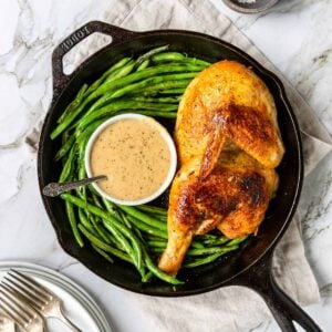 roasted half chicken with crispy golden skin in a skillet with green beans and gravy