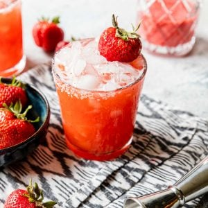 a glass of roasted strawberry margarita garnished with salt and berries