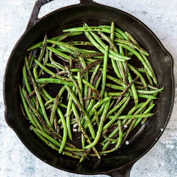 sauteed green beans in a pan with garlic and kosher salt