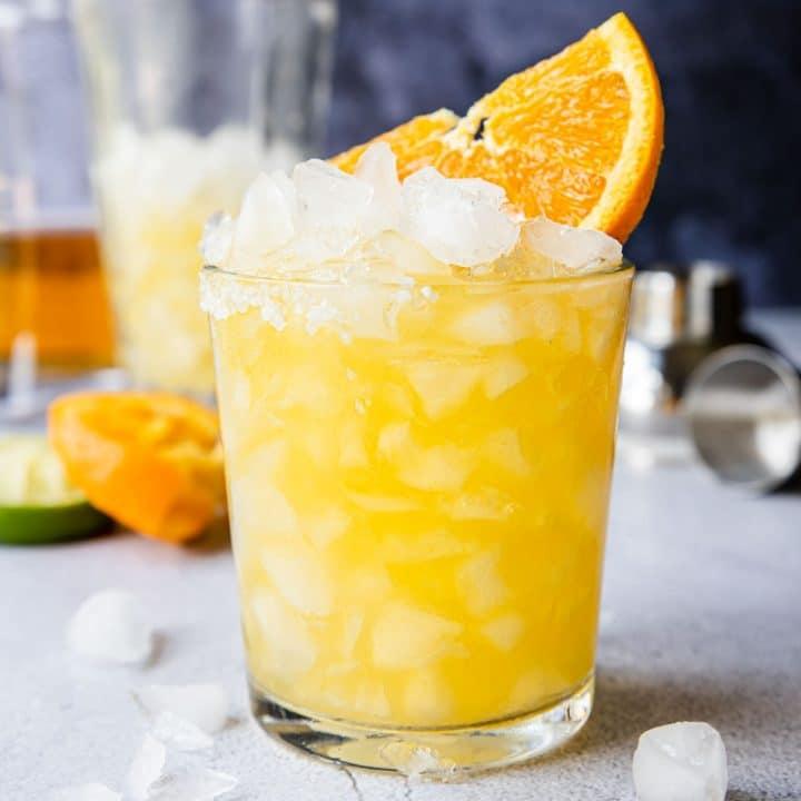 an orange margarita in a glass with an orange wedge