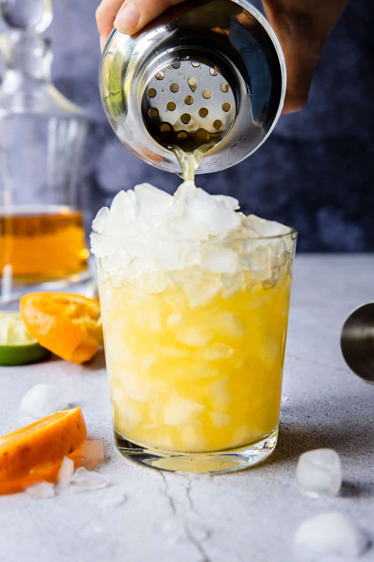 pouring an orange marg from a shaker