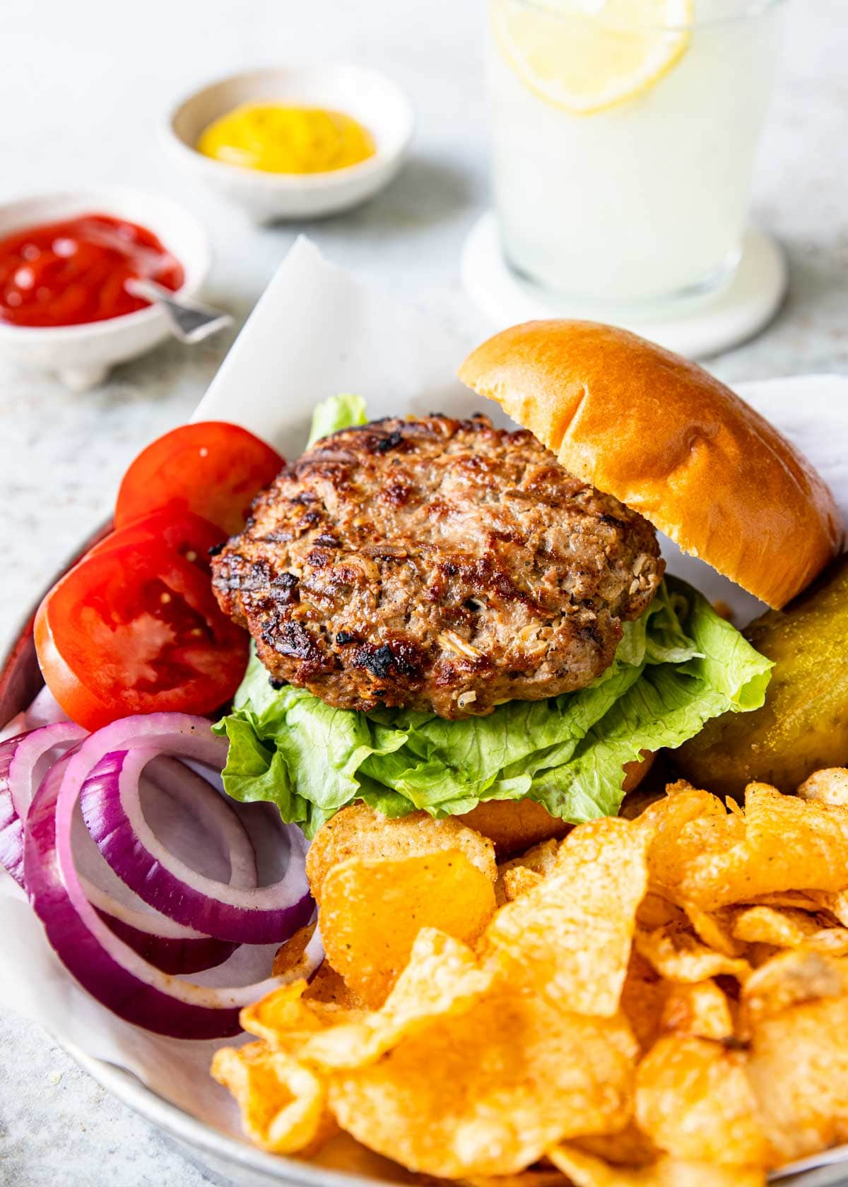turkey burger on a bun with onions and tomatoes to the side