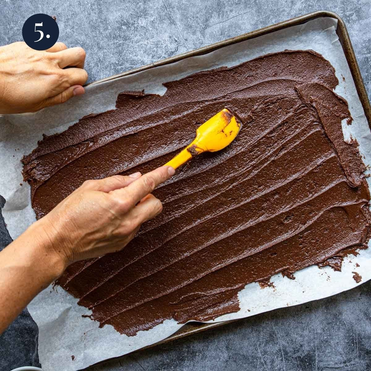 painting brownie brittle batter onto parchment paper