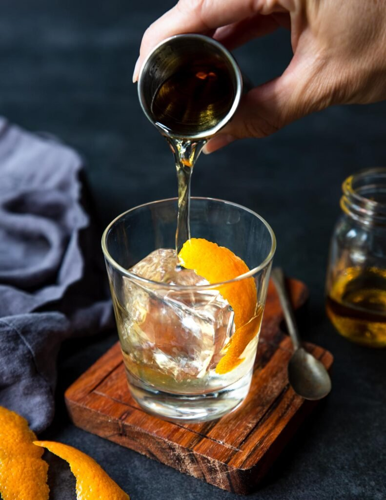 pouring Añejo tequila over a large clear ice cube