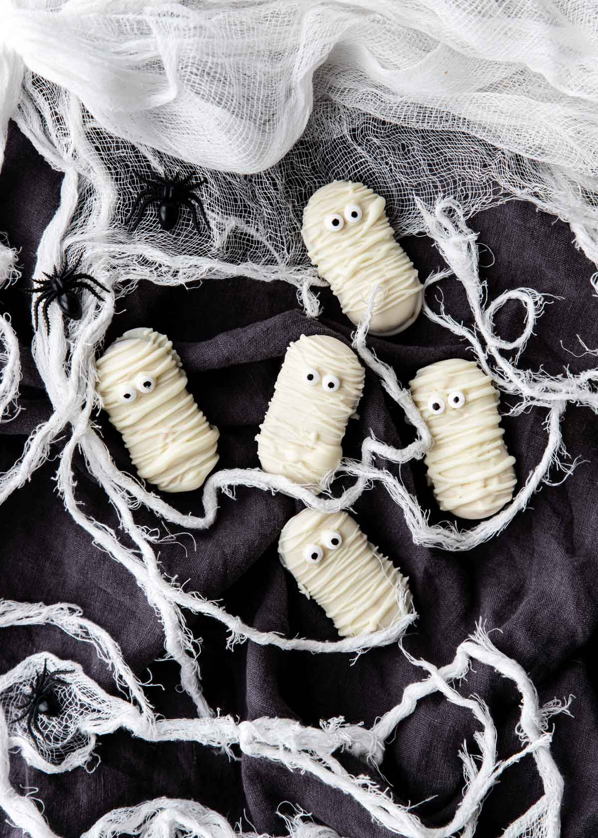 Mummy Cookies on a black surface with gauze around