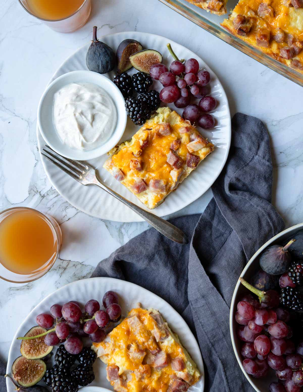 two breakfast plates with ham and egg casserole, fruit and yogurt