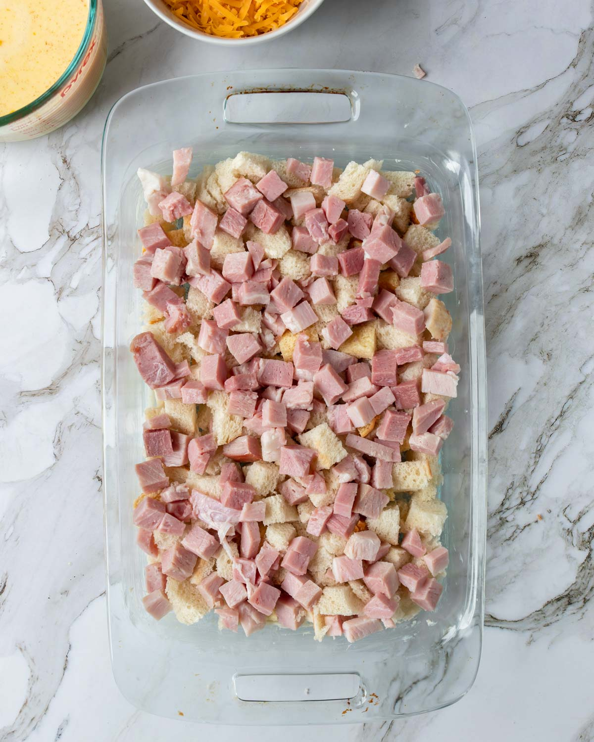 bread cubes and cubed ham in a buttered 9x13 casserole pan
